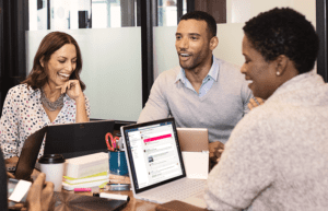 woman and two men sit at desk using microsoft office